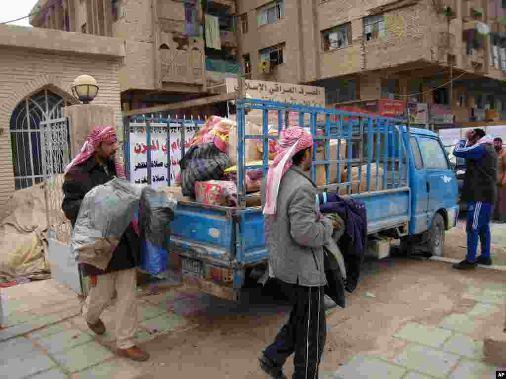 Civilians load their belongings onto a vehicle as they leave their homes after clashes between the Iraqi army and al-Qaida fighters in Fallujah, Jan. 5, 2014.