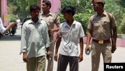 Indian policemen show two men (L and 2nd R), who are accused of gang raping and hanging two girls, to the media at Budaun district in the northern Indian state of Uttar Pradesh, May 30, 2014.