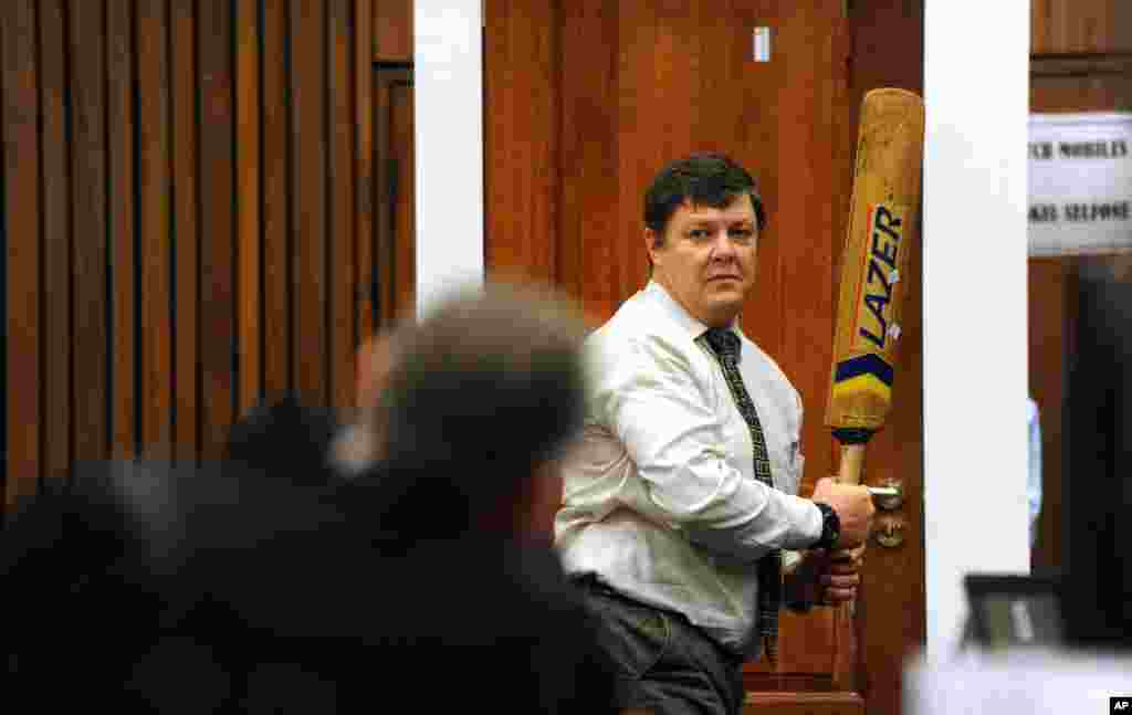 Forensic investigator Johannes Vermeulen, with a cricket bat in hand, demonstrates how Oscar Pistorius could have broken down the bathroom door, Pretoria, March 12, 2014.