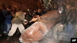 A man with a sledgehammer smashes the toppled statue of Vladimir Lenin in central Kyiv, December. 8, 2013.