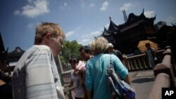 FILE - Foreign tourists visit Yuyuan Garden, one of the most famous tourist destinations in Shanghai, China.