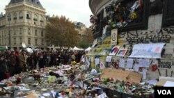 Ratusan orang memberikan penghormatan bagi para korban serangan di Paris, di depan Place de la Republique, Senin (16/11).