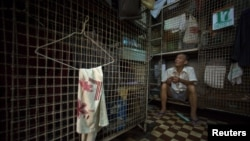 "Kong Siu-kau waits for dinner in Hong Kong's Tai Kok Tsui district, July 16, 2008. As soaring property prices forced rents higher, thousands of Hong Kong residents moved into ""cage homes."""
