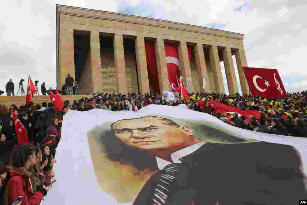 People hold a large image of Mustafa Kemal Ataturk, founder of the Republic of Turkey, outside the Anitkabir, Ataturk's mausoleum, during the 77th anniversary of his death in Ankara.