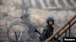 2013年3月12日在韩国首都首尔北面坡州市,靠近朝鲜半岛南北分界线的一个非军事区,一名韩国士兵走上观察站执行任务。