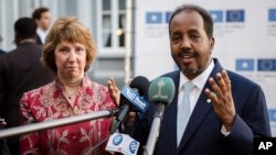 Somalia's President Hassan Sheikh Mohamud, right, gestures a he and European Union Foreign Policy Chief Catherine Ashton address the media prior to an EU Somalia conference in Brussels, Sept. 16, 2013.