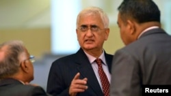 India's Foreign Minister Salman Khurshid speaks to his staff as they attend the 46th Association of Southeast Asian Nations (ASEAN) Foreign Ministers Meeting in Bandar Seri Begawan, July 1, 2013.