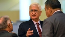 FILE - India's Foreign Minister Salman Khurshid speaks to his staff as they attend the 46th Association of Southeast Asian Nations (ASEAN) Foreign Ministers Meeting in Bandar Seri Begawan, July 1, 2013.