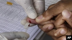 A patient undergoes a pin prick blood test inside a mobile healthcare clinic parked in downtown Johannesburg, 29 Nov 2010