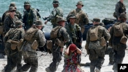 U.S. Marines from Company B, 1st Battalion Landing Team, 5th Marines, 31st Marine Expeditionary Unit and their Philippine counterparts, prepare to board their rubber boat with a mock captured suspect during joint exercises, April 15, 2013.