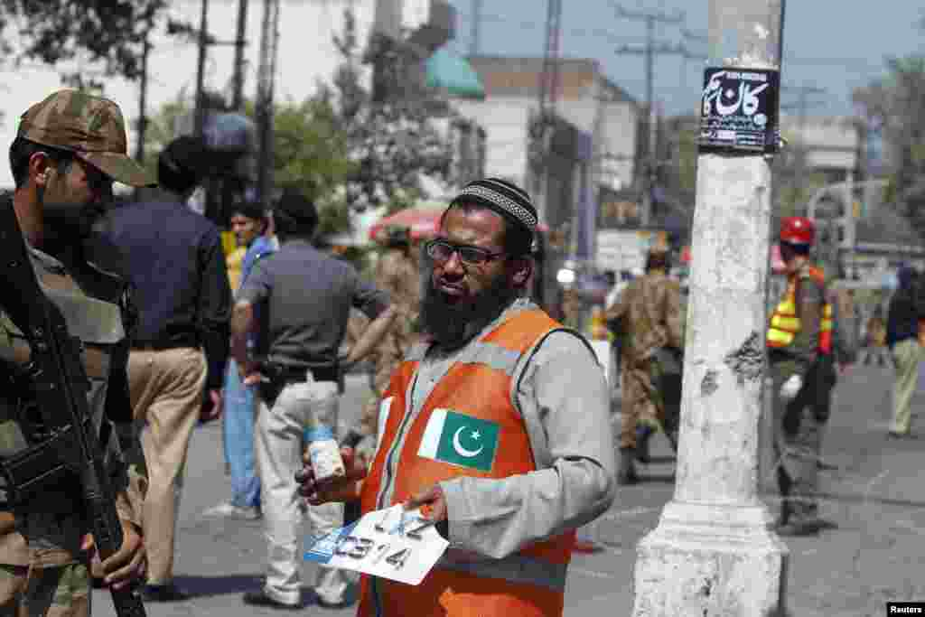 A rescue worker holds a milk bottle and a civilian's vehicle license plate as he collects evidence from the site of a bomb blast in Peshawar, Pakistan, March 29, 2013.