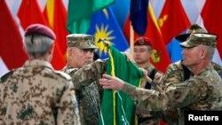 Генерал армії США Джон Кемпбелл, командувач Міжнародними силами сприяння безпеки (МССБ), згортає прапор МССБ на церемонії закінчення воєнної місії в Кабулі, 28 грудня 2014 р.