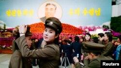 14일 북한 김일성 주석의 102번째 생일을 맞아 여군들이 평양 시내에 마련된 김일성화 전시장 앞에서 사진을 찍고 있다.