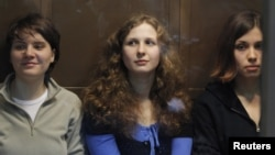 """Members of the female punk band """"Pussy Riot"""" (L-R) Yekaterina Samutsevich, Maria Alyokhina and Nadezhda Tolokonnikova sit in a glass-walled cage before a court hearing in Moscow October 10, 2012."""