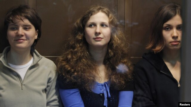 "Members of the female punk band ""Pussy Riot"" (L-R) Yekaterina Samutsevich, Maria Alyokhina and Nadezhda Tolokonnikova sit in a glass-walled cage before a court hearing in Moscow, October 10, 2012."