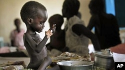 "Two-year-old Nyagod Kuel attempts to eat on her bed in a hospital ward in Akobo, southeastern Sudan, December 2010. The U.N. had once called the region the ""hungriest place on earth."" (File)"