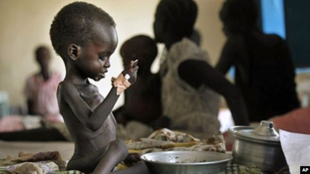 "Two-year-old Nyagod Kuel attempts to eat on her bed in a hospital ward in Akobo, southeastern Sudan. The U.N. mission dubs the ""hungriest place on earth"". (File)"