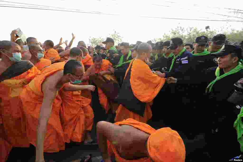 Dhammakaya temple Buddhist monks scuffle with police after they defied police orders to leave the temple grounds to enable police to seek out their former abbot in Pathum Thani, Thailand.