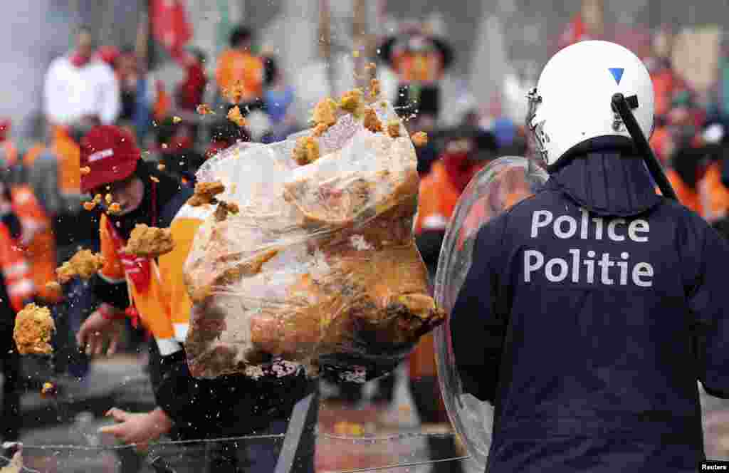 A demonstrator throws garbage towards riot police officers during a European trade unions protest against austerity measures, in central Brussels, Belgium.