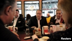 U.S. Republican presidential candidate Mike Huckabee, center, eats lunch with supporters, including former Congressman Duncan Hunter, right, at Drake Diner in Des Moines, Iowa, Feb. 1, 2016.