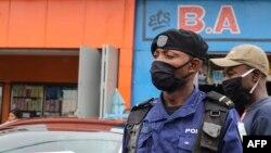Policier moko azipi zolo na munoko na masque na misala mya kolamusa bato mpo na komibatela na COVID-19, na Kinshasa, RDC, 29 mai 2020.