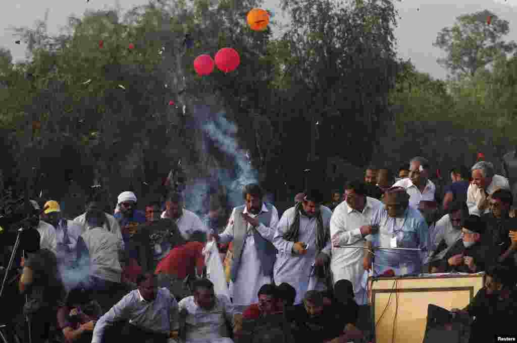 Những người đàn ông và những người ủng hộ phản ứng sau khi một loạt bong bóng nổ trên sân khấu nơi ông Mohammad Tahir ul-Qadri (phải, tại bàn), một giáo sĩ Sufi và là lãnh đạo đảng phái chính trị Pakistan, Tehreek Awami (PAT), đang phát biểu trước đám đông trong cuộc Diễn hành Cách mạng ở Islamabad.