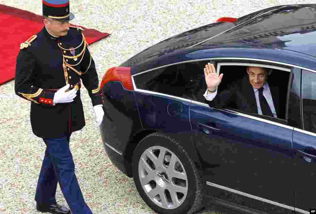 Tổng thống xuất nhiệm Nicolas Sarkozy vẫy chào khi rời khỏi Ðiện Elysee (AP)