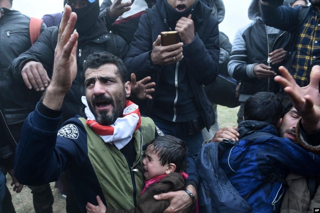그리스 북부 테살로니키의 난민 캠프 밖에서 시위가 발생한 가운데 남성이 아이들이 울자 항의하고 있다. 이 날 난민 수백병은 그리스 국경이 열렸다는가짜뉴스를 듣고 다른 유럽연합 국가로 넘어가겠다며 북마케도니아 국경을 향해 행진하다 경찰과 충돌했다.