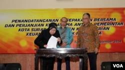 Walikota Surabaya Tri Rismaharini menandatangani naskah perjanjian kerjasama pendataan wajib pajak berbasis internet antara Pemkot Surabaya-Kementerian Keuangan, disaksikan Menkeu Chatib Basri (tengah) dan Dirjen Pajak Fuad Rahmany (kanan), 9 September 2014 (Foto: VOA/Petrus Riski)