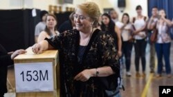In this photo released by Presidencia of Chile, Chilean President Michelle Bachelet casts her vote during presidential elections in Santiago, Nov. 19, 2017.