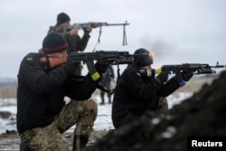 FILE - Ukrainian servicemen fight at their position near Lysychansk, in the Luhansk region, Jan. 29, 2015.