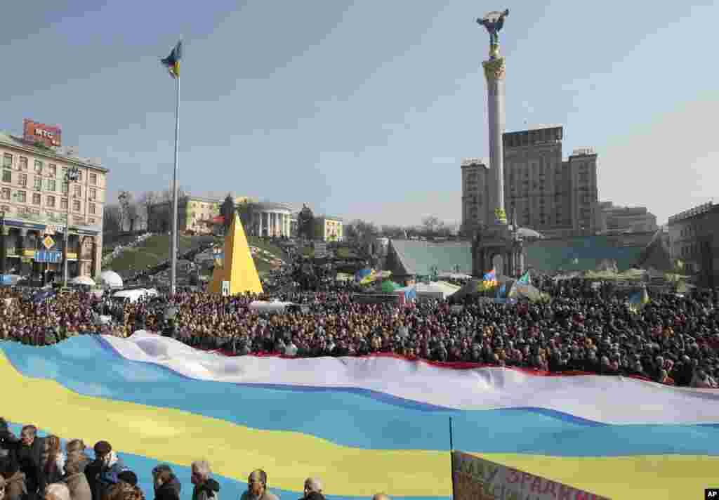 People hold Ukrainian, Crimean and Crimean Tatar flags during rally in support of Ukraine's territorial integrity, in Kyiv's Independence Square, March 23, 2014.