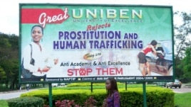A student at Nigeria's Benin University in Benin City walks past a billboard encouraging women to fight human trafficking.