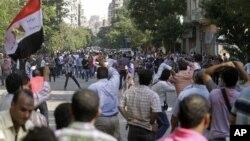 """Trên các đường phố Cairo hôm thứ Sáu, những người ủng hộ ông Morsi hô to khẩu hiệu """"dân muốn tẩy sạch bộ máy tư pháp!"""" trong khi người người chống đối hô: """"dân muốn lật đổ Tổng thống!"""""""
