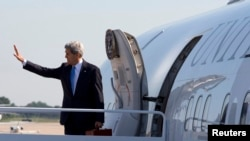 U.S. Secretary of State John Kerry waves as he boards his plane at Andrews Air Force Base in Maryland on his way to Doha, June 21, 2013.