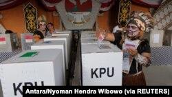 Petugas pemilihan mengenakan pakaian adat Papua saat pemilihan di TPS 17 April 2019. (Foto: Antara/Nyoman Hendra Wibowo via Reuters)