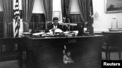El presidente John F. Kennedy sentado en la oficina oval de la Casa Blanca mientras su hijo John F. Kennedy Jr. se esconde por debajo del escritorio.