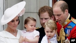 Britain's Prince William holding Prince George, right and Kate, Duchess of Cambridge holding Princess Charlotte, left, on the balcony at Buckingham Palace.