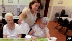 Cristina Couto, supervisor at Ironbound Senior Center, pours water for elderly bingo players, Newark, New Jersey, June 21, 2012.