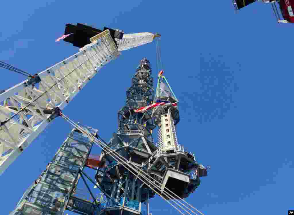 The silver spire topping One World Trade Center is lifted as it is fully installed on the building's roof, bringing the structure to its full, symbolic height of 1,776 feet (541 meters), May 10, 2013 in New York.