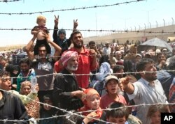 FILE - Syrian refugees gather at the Turkish border as they flee intense fighting in northern Syria between Kurdish fighters and Islamic State militants in Akcakale, southeastern Turkey.