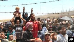 FILE - Syrian refugees gather in Akcakale, southeastern Turkey, after fleeing intense fighting, June 15, 2015.