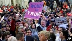Kandida Donald Trump leve anlè yon postè yon patizan li te lonje ba li aprè li te fin pale nan yon meeting elektoral nan vil Bethpage, nan Eta New York, mèkredi 6 avril 2016 la.