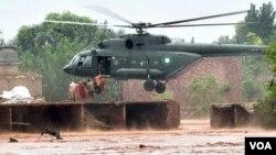 Petugas pertolongan berusaha mengevakuasi penduduk yang terjebak akibat bencana banjir.