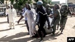 Les forces de sécurité transportent dans une couverture les restes d'un victime d'explosion dans le nord de la ville de Maroua, Cameroun, 22 juillet 2015.