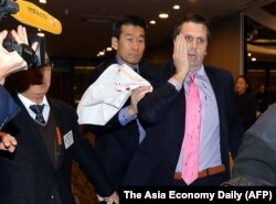 美国驻韩国大使李柏特(右)用手按住脸部刀伤离开世宗文化会馆