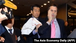 U.S. ambassador to South Korea Mark Lippert covers a cut on his face after he was attacked by a man with a knife in Seoul, March 5, 2015.