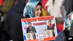FILE - A protestor shows pictures of detained Turkish HDP politicians Selahattin Demirtas and Figen Yuksekdag at a demonstration against Turkish president Recep Tayyip Erdogan and political repression that followed July's failed military coup, Cologne, Germany, Nov. 12, 2016.