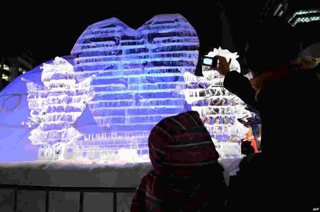 Khách viếng thăm nhìn những điêu khắc trên băng trong lễ hội tuyết Sapporo thường niên ở Sapporo Nhật Bản với tổng cộng 198 tượng bằng tuyết được trưng bày và hy vọng hấp dẫn khoảng hai triệu khách tham quan.
