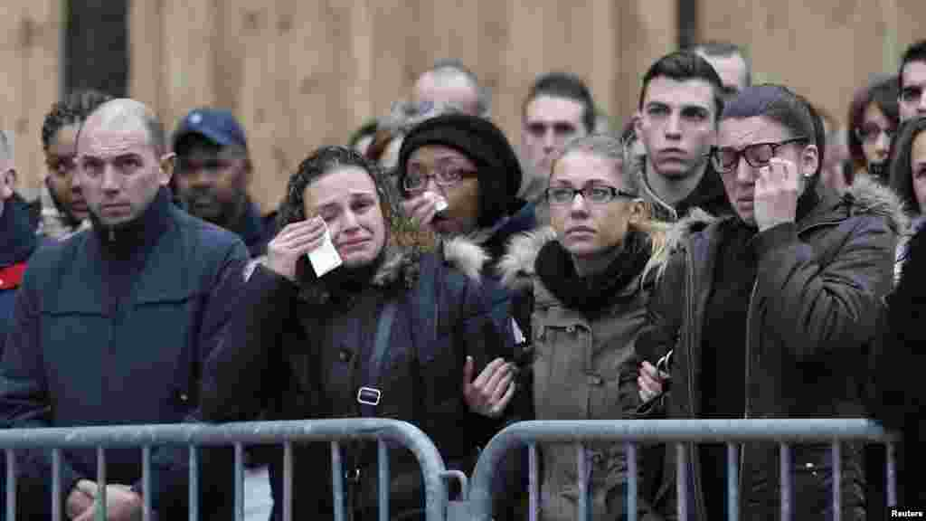 People react as they attend a national tribute for the three officers killed during last week's terrorist attacks, in front of Paris Prefecture, Jan. 13, 2015.